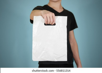 Man shows white blank plastic bag mock up isolated. Empty white polyethylene package mockup. Consumer pack ready for logo design or identity presentation. Commercial product food packet handle