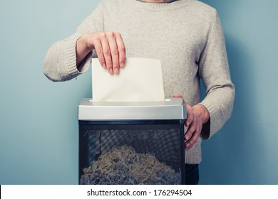 Man is shredding a piece of paper