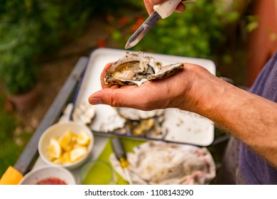 A man shucking oysters with an oyster knife