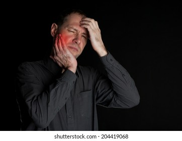 Man with a sick tooth keeps cheek hand. On a black background