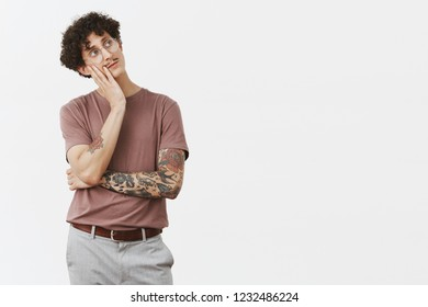 Man sighing feeling bored thinking what to do. Indifferent gloomy handsome white male with moustache and curly hairstyle leaning on palm gazing at upper right corner careless with boring expression