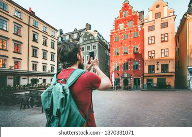 Man sightseeing Stockholm city Stortorget landmarks traveling lifestyle taking photo by smartphone Europe trip summer vacations