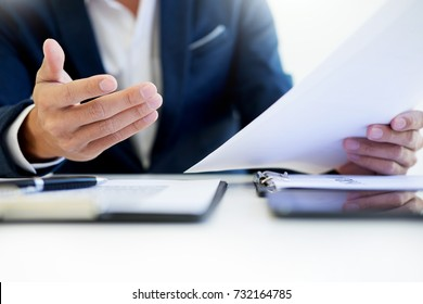 Man signing a car insurance policy, the agent is holding the document
