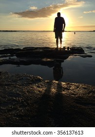 Man silhouette beach rocks mauritius sunset