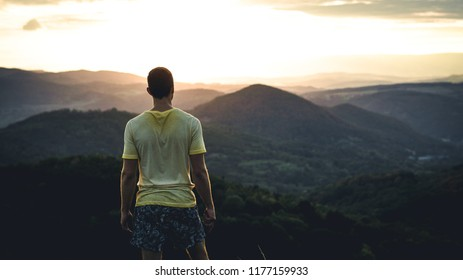 Man silhouette climbing high on cliff. Hiker has climbed up to peak enjoy view. Man watching the sunset, Czech nature