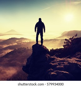 Man silhouette climbing high on cliff. Hiker climbed up to peak enjoy view. Man  watch over misty and foggy morning valley in morning Sun.
