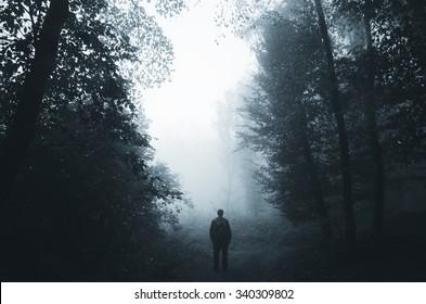 man silhouette in dark foggy forest