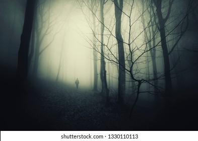 man silhouette in dark scary woods, halloween landscape with strange figure walking in gloomy forest