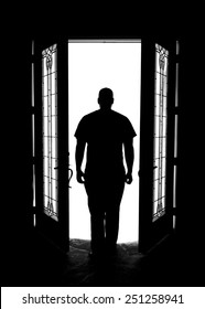 Man silhouette in doorway with glass windows arms at sides looking out while mysterious solitary meditative reflective lonely thoughtful patient dangerous serious imagining and white light symbolism