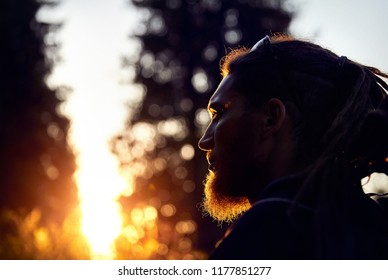 Man silhouette with dreadlocks in sunset mountain forest