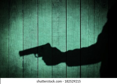 Man in silhouette with gun ready to shoot on natural wooden background, with space for text or image.