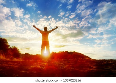 Man Silhouette with Hands Up on the Sunset Background