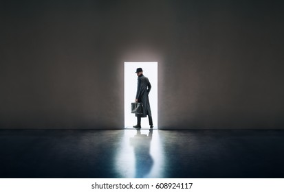 Man silhouette in hat and raincoat standing in the light of opening door in dark room