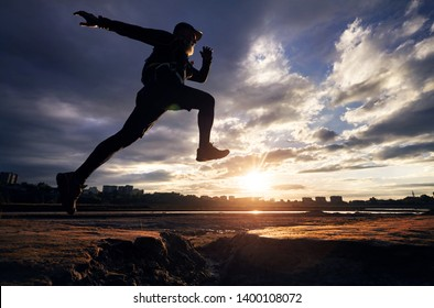 Man in silhouette jump running against cloudy sunset sky