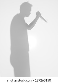 man silhouette with kitchen knife in his hand standing from profile, with a gesture of attacking someone,  behind a diffuse surface