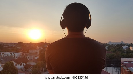 Man silhouette listening to the headphones on the sunset landscape background.