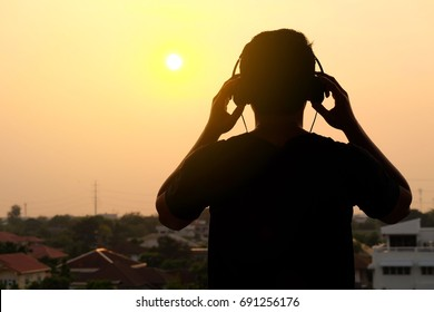 Man silhouette listening to the headphones on the sunset landscape background