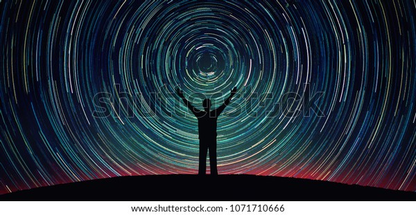 Man silhouette on a night sky background with bright stars trails. Man watching the stars. Science, education and religion team concept background. Elements of this image furnished by NASA.
