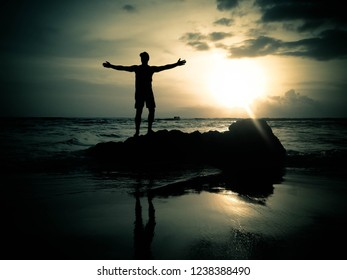 Man Silhouette On The Sea Rocks In The Sunset Light At Batu Bolong Beach, Canggu Village, Badung, Bali, Indonesia