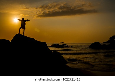 Man Silhouette on stone at sea sunset time.