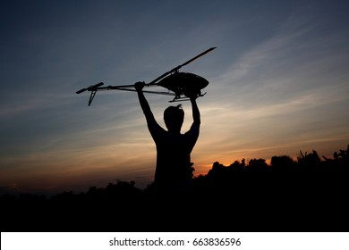 Man silhouette with RC copter at sunset.