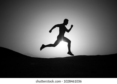 man silhouette, running guy on sunset fiery sky background in mountain, sport and recreation, future and success, people and nature, speed and healthy lifestyle, copy space