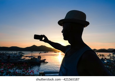 ba6b7b02d8b4c Man silhouette selfie at sunset with lagoon landscape at Philippines Island  - Tourist male taking self