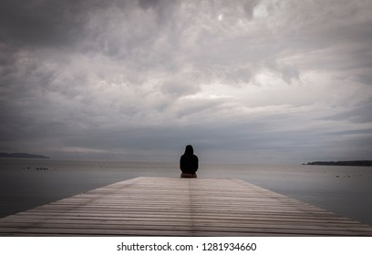 A man silhouette sitting on wooden pier lonely at the sea in the morning clouds.