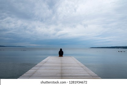 A man silhouette sitting on wooden dock lonely at the sea in the morning clouds.