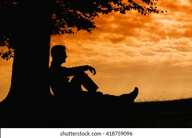 Man silhouette sitting under tree on cloudy day outdoor