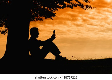 Man silhouette sitting under tree with tablet on cloudy day outdoor