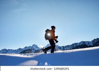 Man in silhouette skiing on fresh powder snow at the mountains against sunny sky near Almaty, Kazakhstan