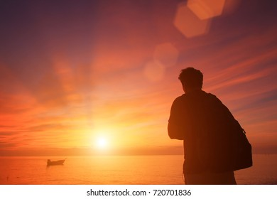 Man silhouette stand alone on the beach and watching romantic colorful sunrise