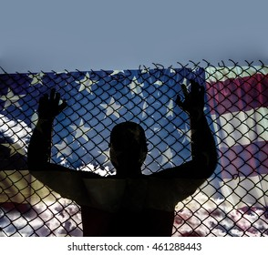 man silhouette stand near black metal Net - barbed wire against american flag and blue sky