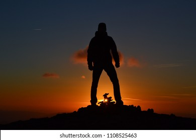 Man silhouette standing on the mountain peak while orange sunset. Strong, powerfull, successful man with his hands in fist. Outdoor background.