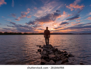 Man silhouette, standing on river stones gangway and contemplating a beautiful sunset.