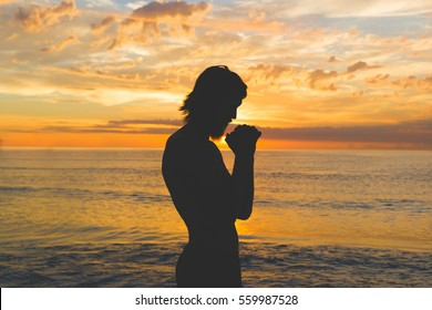 man silhouette standing on sea sunset and holding hands in praying gesture, making a wish