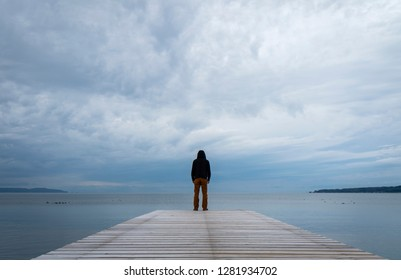A man silhouette standing on wooden pier lonely at the sea in the morning clouds.