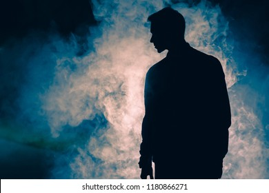 The man silhouette standing in the smoke. evening night time