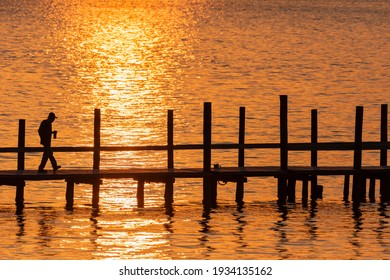 A man in silhouette takes a stroll along a pier as the sun sets over Mobile Bay in Fairhope, AL, USA, on October 21, 2020.