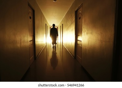man silhouette walking through a lit corridor, which conveys the concepts of rebirth,evolution and achievement
