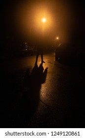 A man silhouetted by a street lamp on a dark street at night, has a sinister, dramatic feel.