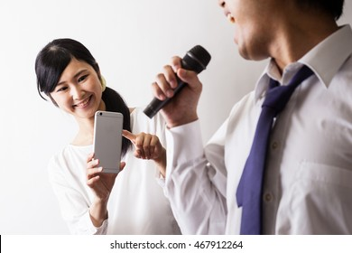 Man to sing in karaoke and Woman taking a photo, mobile phone