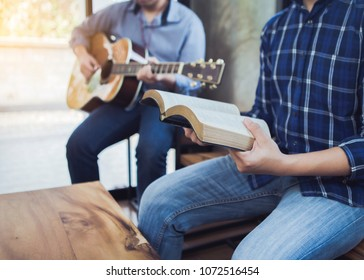 a man sing a song from hymn book while his friends playing guitar indoor