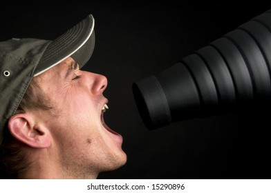 Man singing in front of a snoot, against a black background.