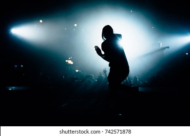 Man singing in front of the stage crowd. Singer doing his best at the concert.