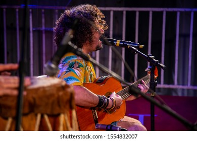Man singing and playing acustic guitar at a concert