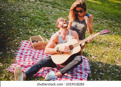 Man singing and playing guitar to his girlfriend on a picnic