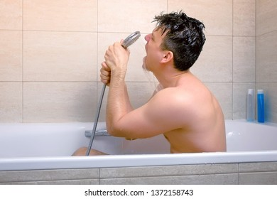 Man is singing with shower as a microphone while he is washing in bathtub. He pours water on his head with shower. Side view.
