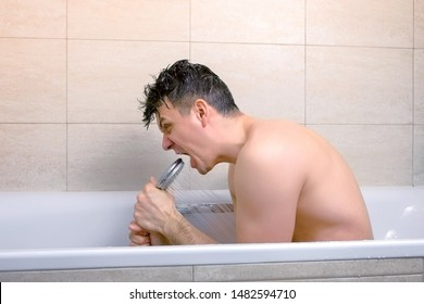 Man is singing with shower as a microphone while he is washing in bathtub. Side view.